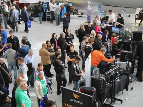A crowd of visitors looking and trying out PC systems for flight sim
