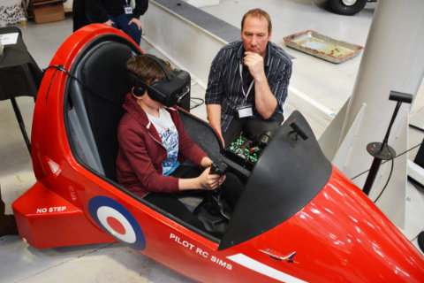 A younger visitor trying out a Hawk cockpit setup with VR