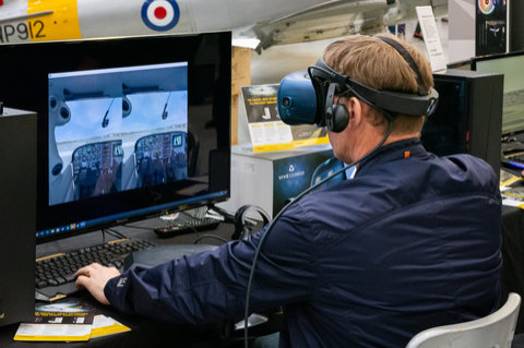 A visitor tries out flight simulator in VR